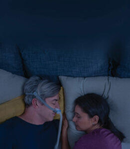 Man sleeping with AirFit N30 CPAP mask close to his wife-mobile image-ResMed Middle East